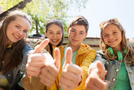 teenage friends or students showing thumbs up